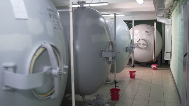 Huge storage tanks for alcoholic beverages at factory. Steel barrels for fermentation of tincture in distillery. In containers support certain conditions for obtaining tasty and high-quality alcohol. - video