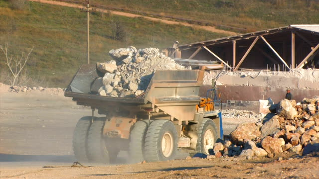 Huge truck pour ore into hopper crushers for further processing. video