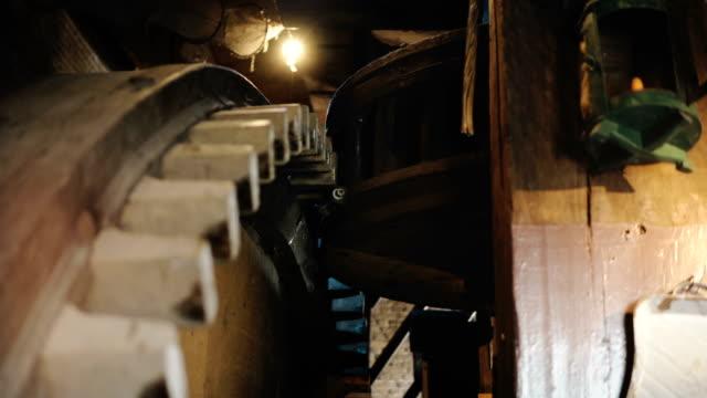 4k riesige hölzerne windmühle zahnräder drehen langsam. traditionelle alte holländische mühle mechanismus in nahaufnahme zahnräder drehen - zahnräder stock-videos und b-roll-filmmaterial
