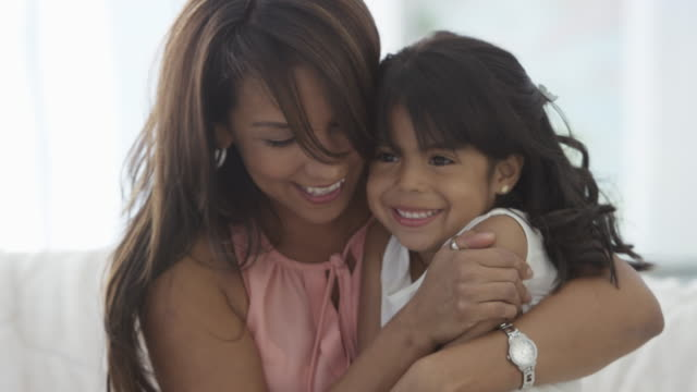 Hugging Mother A young girl and her mother smile and cuddle on the couch. mothers day stock videos & royalty-free footage