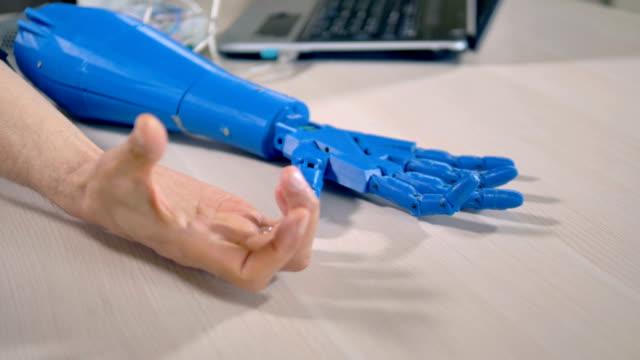 a human arm clenches a tight fist to test a bionic hand. - часть машины стоковые видео и кадры b-roll
