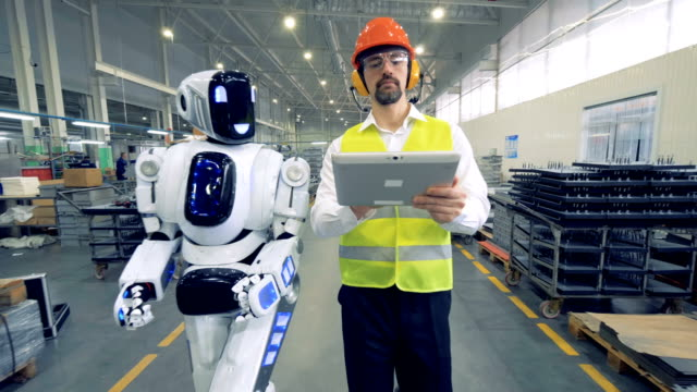 vídeos de stock e filmes b-roll de human factory worker and a robot are walking together in factory premises - technology