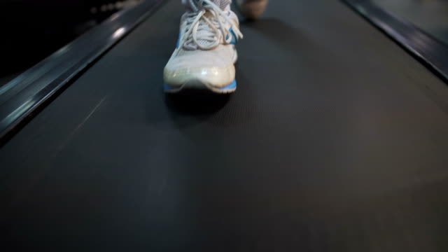 human feet in sport shoes walking on treadmill in gym, rehabilitation center - runner rehab gym video stock e b–roll