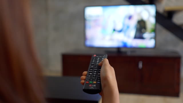 vídeos de stock e filmes b-roll de human hand changes the channels on the tv remote control - led painel
