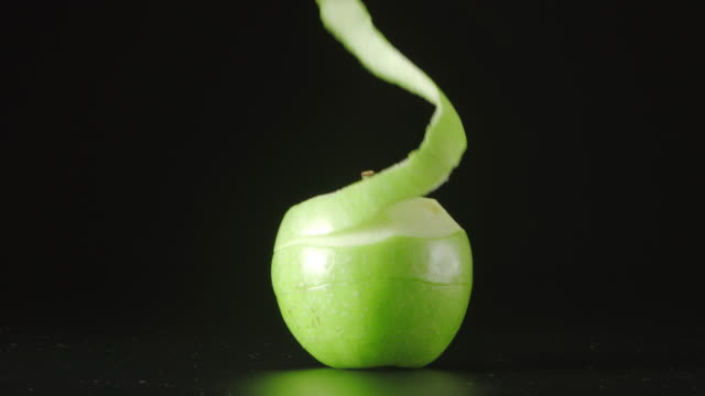 Human hand cleans a green apple (a spiral) video