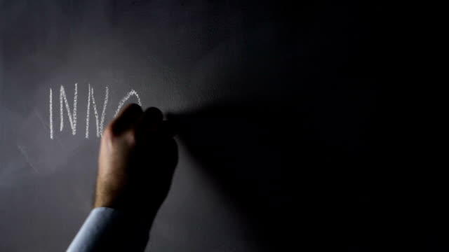Human hand drawing INNIVATION on blackboard video