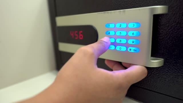 Human hand entering pin for closing and locking the digital safe box