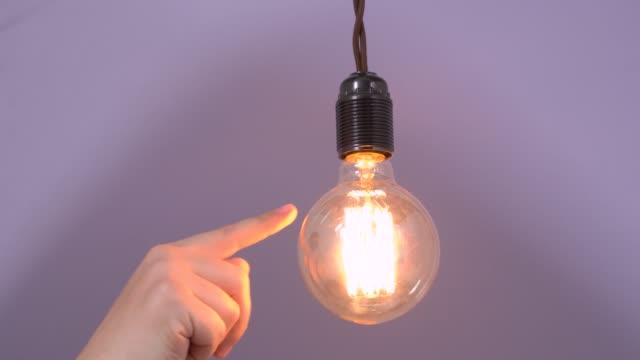 vídeos y material grabado en eventos de stock de la mano humana toca suavemente la bombilla luminosa que cuelga del alambre con el dedo, la desenrosca de la base y la retuerce hacia atrás. fijación y prueba de equipos de electricidad e iluminación - descarga eléctrica