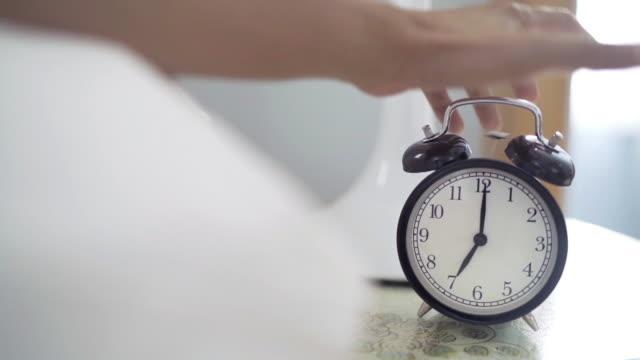 human hand grab alarm clock at seven o'clock in the morning - sonnecchiare video stock e b–roll