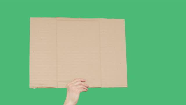 menschliche hand hält leeren karton auf grünem chromakey-bildschirmhintergrund. unkenntliche männer, die pappbanner auf leerem grünem bildschirm zeigen. - spruchband stock-videos und b-roll-filmmaterial