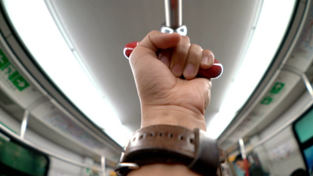 POV Human Hand Holding Handrail or Grip Straps in Subway or Train