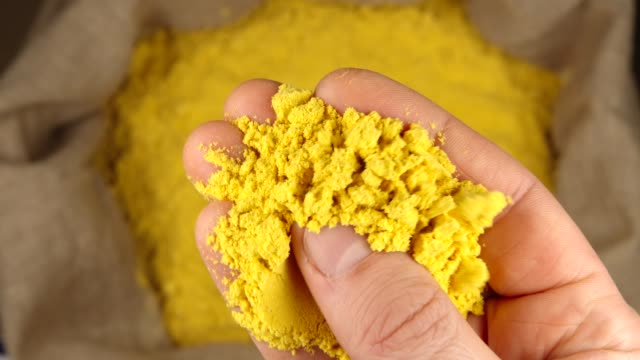 TOP VIEW: Human hand holds and presses a pinch of a turmeric (curcuma) powder over a sac TOP VIEW: Human hand holds and presses a pinch of a turmeric (curcuma) powder over a sac sac stock videos & royalty-free footage