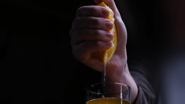 Human hand is squeezing orange into the drinking glass of orange juice video