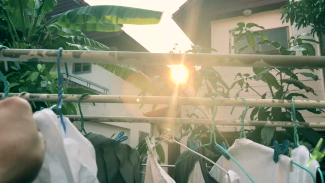human hand keeping clothing drying on clothes rack , scene with sun flare , birdsong surrounding