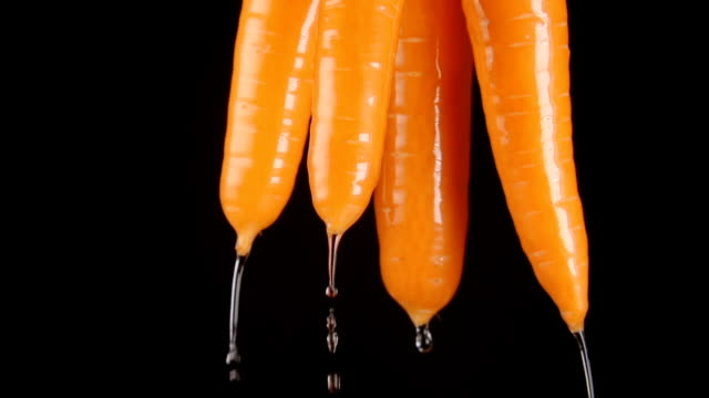 SLOW MOTION: Human hand lifts a carrots from a water - drops falls (black background) video