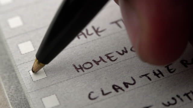 Human hand marking done task on to do list, checklist tick placed on chore notebook