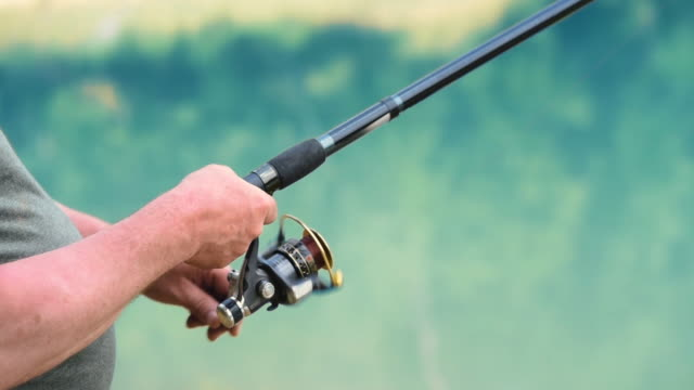 Human hand rotating a fishing reel Human hand rotating a fishing reel fishing rod stock videos & royalty-free footage