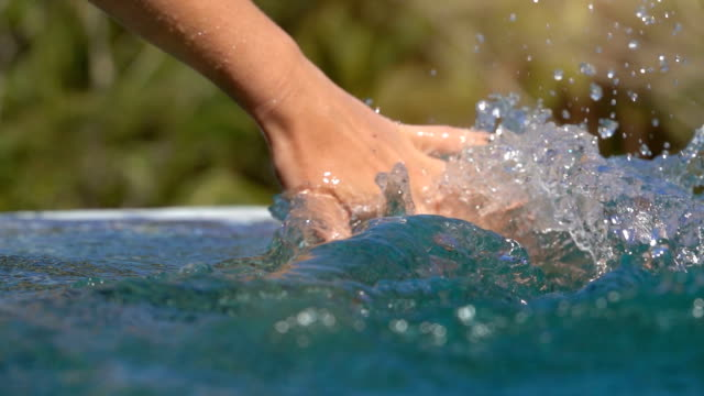SLOW MOTION Human hand sliding through water surface splashing drops in pool video