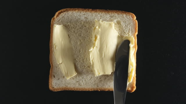 Human hand spreads a butter on a bread video