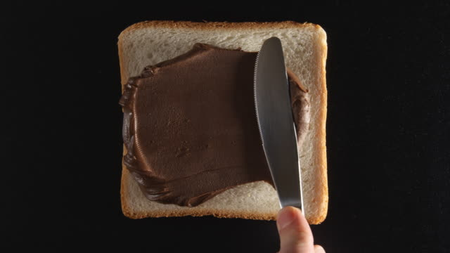Human hand spreads a chocolate paste on a bread video