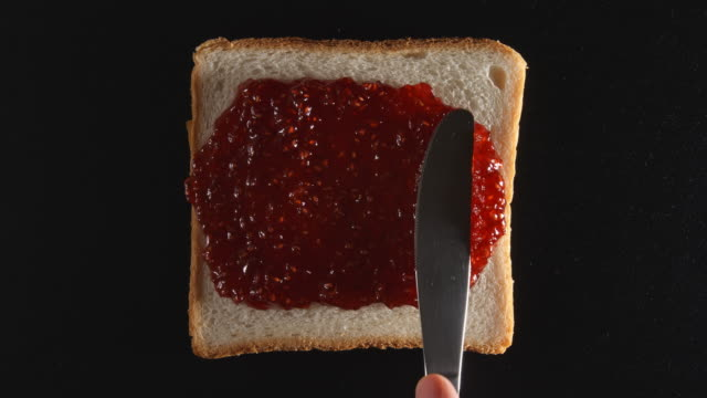 Human hand spreads a raspberry jam on a bread Human hand spreads a raspberry jam on a bread jello stock videos & royalty-free footage