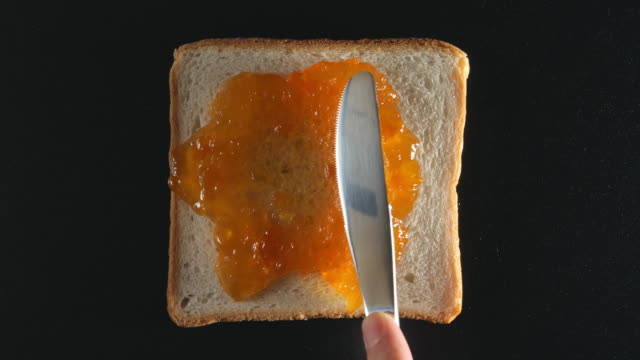 Human hand spreads an apricot jam on a bread video