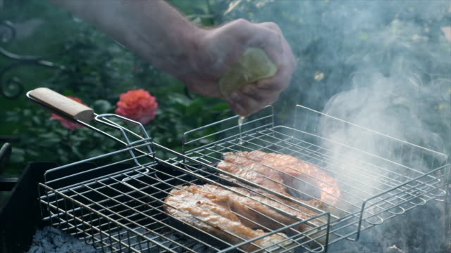 Human hand squeezing lime juice on fish on the lattice on barbecue. Salmon red fish on a grill. Grilling trout steaks. Chef squeezes a half cut lemon over fish Human hand squeezing lime juice on fish on the lattice on barbecue. Salmon red fish on a grill. Grilling trout steaks. Chef squeezes a half cut lemon over fish. Cooking Roasted fish on the open fire. Barbecue, outside. Village lifestyle. Slow motion fillet stock videos & royalty-free footage