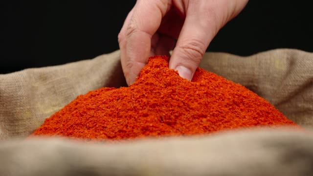 Human hand takes a pinch of a red pepper powder from a top of pile in a sac Human hand takes a pinch of a red pepper powder from a top of pile in a sac sac stock videos & royalty-free footage