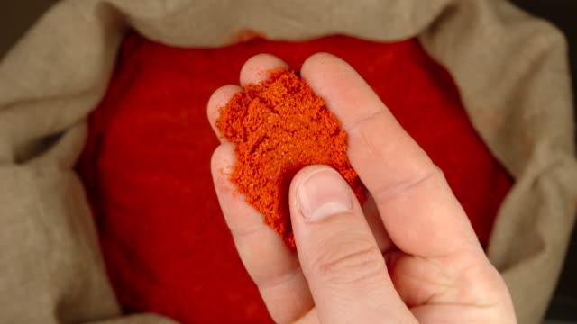 vídeos y material grabado en eventos de stock de vista superior: la mano humana toma una pizca de pimiento rojo de un saco - cayena guindilla roja
