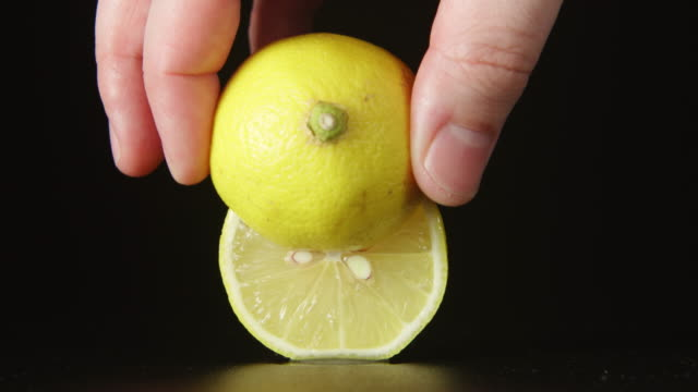 Human hand takes away a half of lemon video