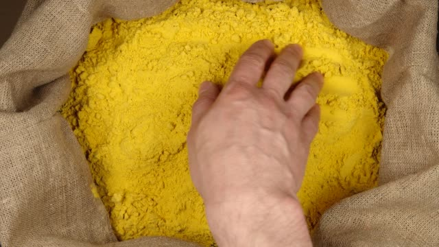 TOP VIEW: Human hand touching a turmeric (curcuma) powder in a sac TOP VIEW: Human hand touching a turmeric (curcuma) powder in a sac sac stock videos & royalty-free footage