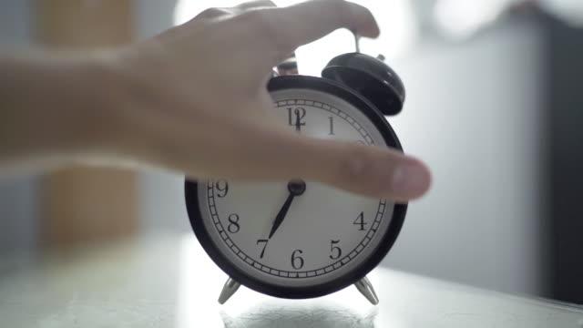 human hand turn off alarm clock at seven o'clock in the morning - sonnecchiare video stock e b–roll