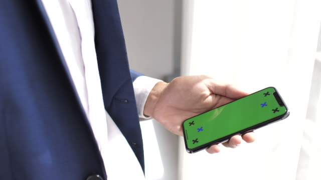 Human hand using green screen mobile phone, iPhone X