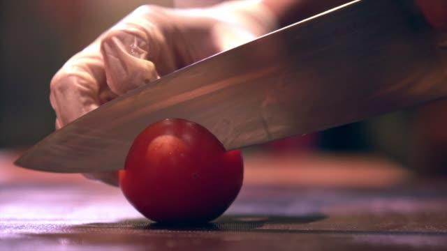 vidéos et rushes de main humaine avec des légumes de coupe de gant sur un tableau d'oral avec la compétence de précision de coupe de tomate de couteau - tomate