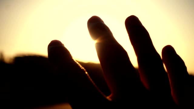 human hand with light of sun - modlić się filmów i materiałów b-roll