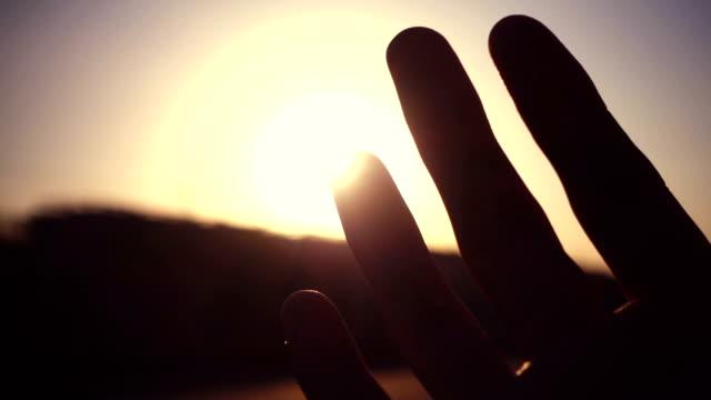 vidéos et rushes de main de l'homme avec la lumière du soleil - naissance