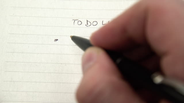 Human hand writing tasks on to do list, chore checklist in notebook