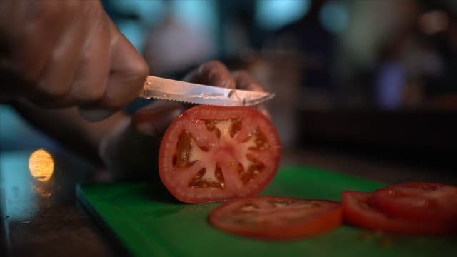 Human hands cut tomatoes on a cutting board at restaurant
