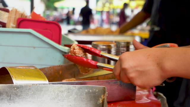 Human hands cutting serving size of fried sausage at food stall