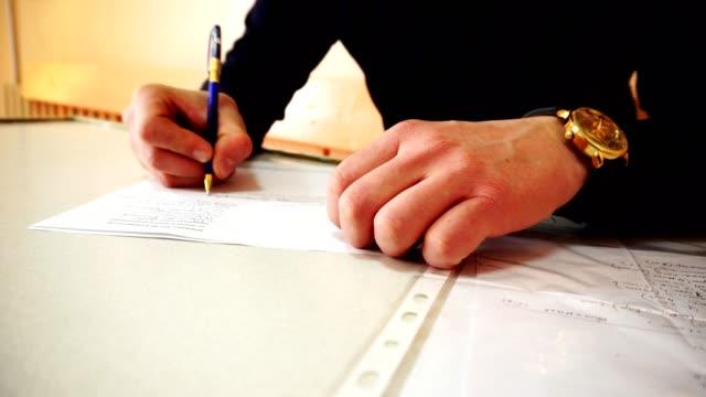 Ein Mensch die Hände füllen Dokumente oder einen Brief zu schreiben. Video Nahaufnahme. – Video