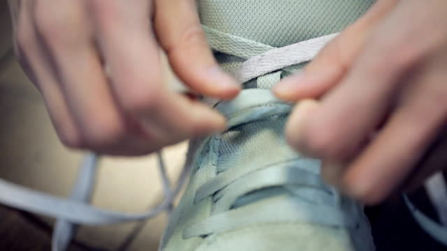 Human Hands hastily knotted bright light long laces on sneakers video