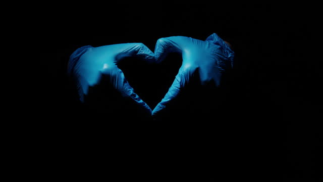 Human hands in surgical gloves are showing a heart shape video