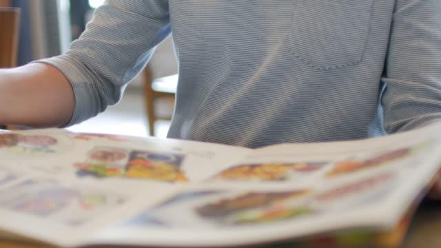 vidéos et rushes de des mains humaines ouvrir un menu au restaurant - recette