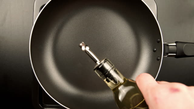 TOP VIEW: Human hands pouring olive oil on the frying pan TOP VIEW: Human hands pouring olive oil on the frying pan cooking pan stock videos & royalty-free footage