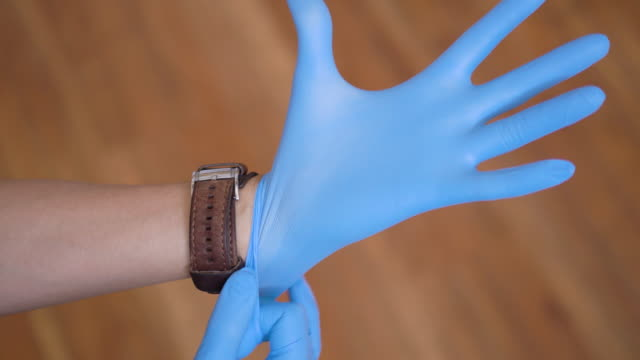 Human hands putting on medical rubber gloves Human hands putting on medical rubber gloves glove stock videos & royalty-free footage