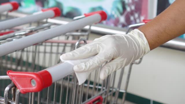 Human hands spraying alchohol and rub shopping cart handle