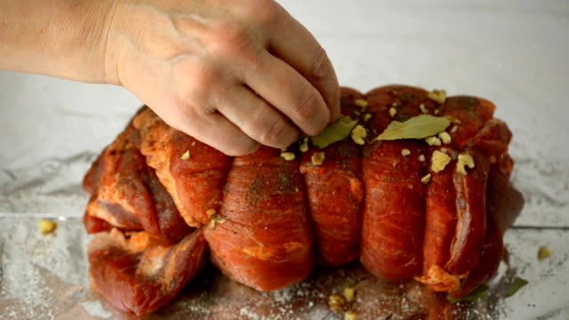 Human hands sprinkle spices and nuts, raw marinated tied with string roll of pork. video