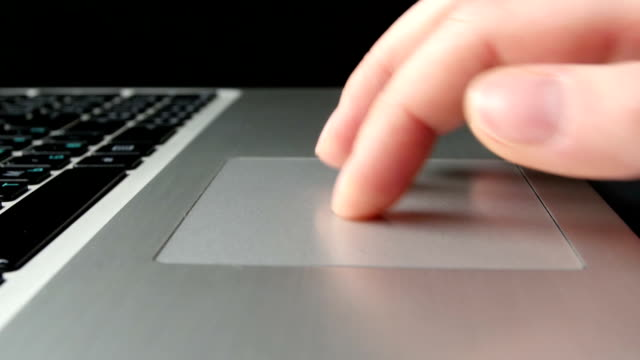 Human hands working on laptop, close up, side view, black video