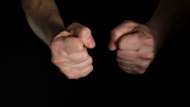 vídeos de stock, filmes e b-roll de palma masculina humana aperta um punho isolado em fundo preto. feche minuciosamente. - punho