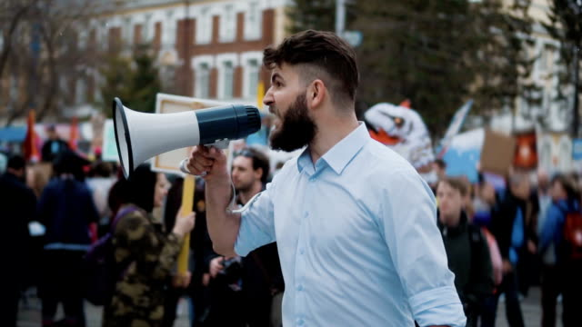 Human on the background of the crowd on the revolution. office worker slowmotion Young adult angry man goes and shouts in a megaphone on strike. Caucasian guy with a beard yelling into the loudspeaker at the rally. Office worker displeased with dismissal or reduction slow motion.. megaphone stock videos & royalty-free footage